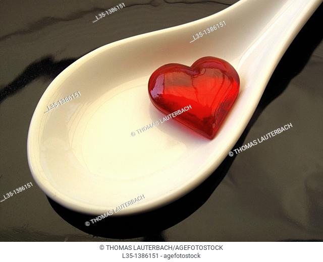 Small glass heart is in medicine spoon