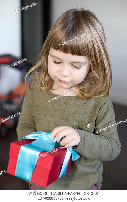 portrait of three years old caucasian blonde child, with green shirt, and red and blue gift box in hands indoors