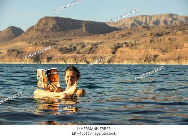 Woman reading a guidebook in Dead Sea, Jordan, Middle East