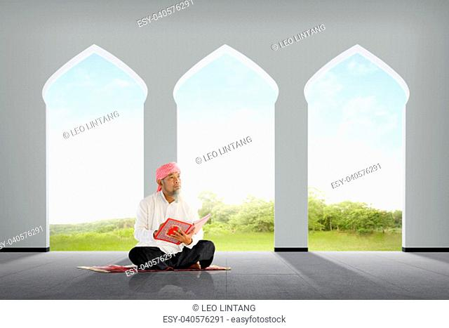 Senior asian muslim man sitting with Koran inside the mosque