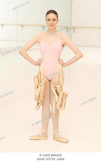 A young ballerina holding ballet shoes