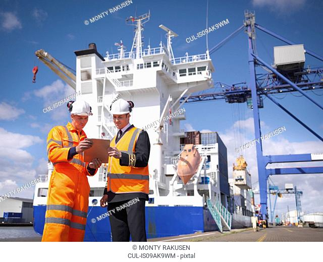 Ship's captain discussing loading cargo with port worker
