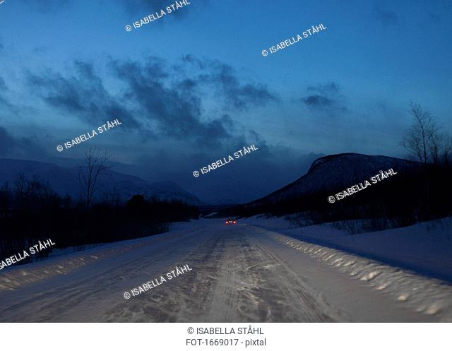 Distant view of car on snow covered road against sky at dusk, Kiruna, Sweden