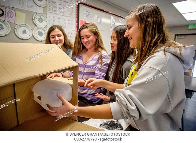 Mission Viejo, CA, middle school female students improvise a filter for storm drain water using a cardboard box, a plastic bottle