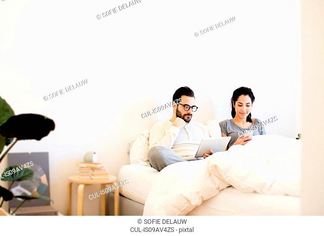 Young couple sitting up in bed using digital tablet and smartphone