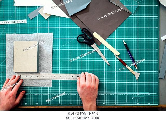 Overhead detail of hands, paper, cutting mat, ruler, scalpel and scissors in print studio