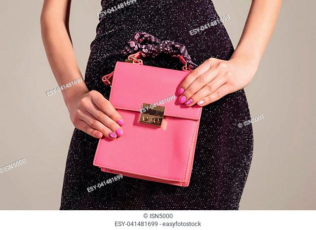 Elegant girl with pink leather handbag in hand