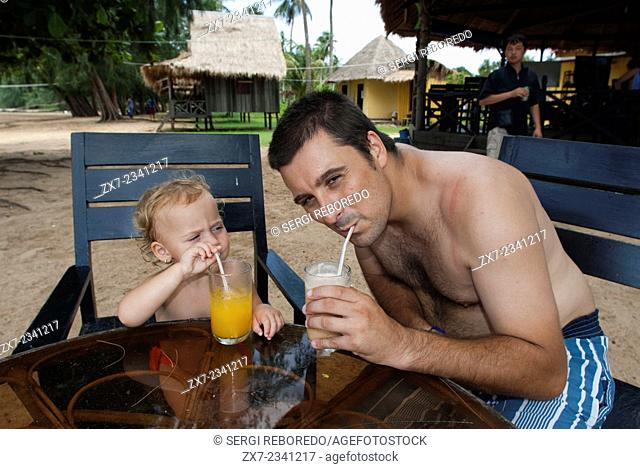 Taking breakfast in Beach on the island of Koh Russei. Cambodia. Travel with children's. Father traveling with her daughter