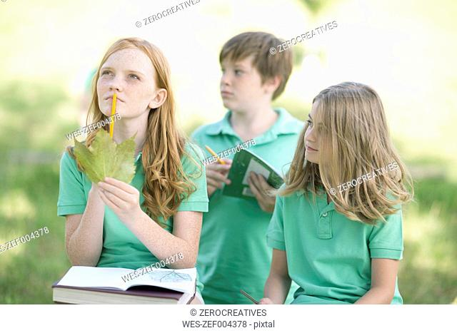 Portrait of girl with exercise book and leave in a park