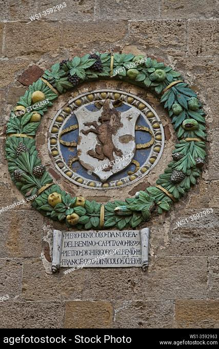 Coat of arms of noble families in a wall in the old town of Volterra, Tuscany, Italy
