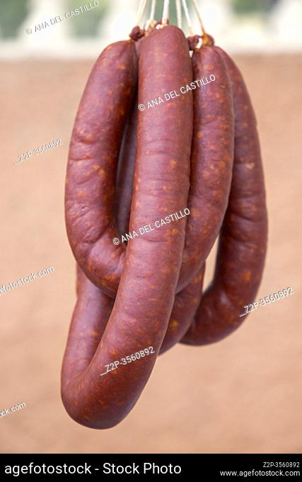Strings of Hand Crafted Artisanal Sausages Red Chorizo Hanging at Farmers Market. Spain