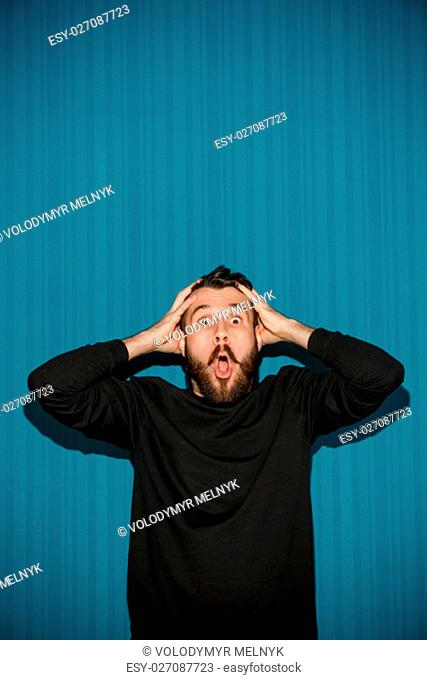 Portrait of young man with shocked facial expression over blue studio background