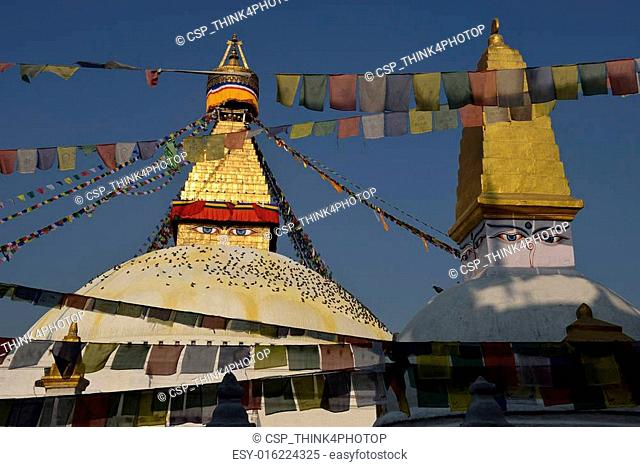 Boudhanath Stupa. Golden spire and all seeing Buddha eyes on top a giant white hemisphere. Smaller stupa in foreground. Kathmandu, Nepal