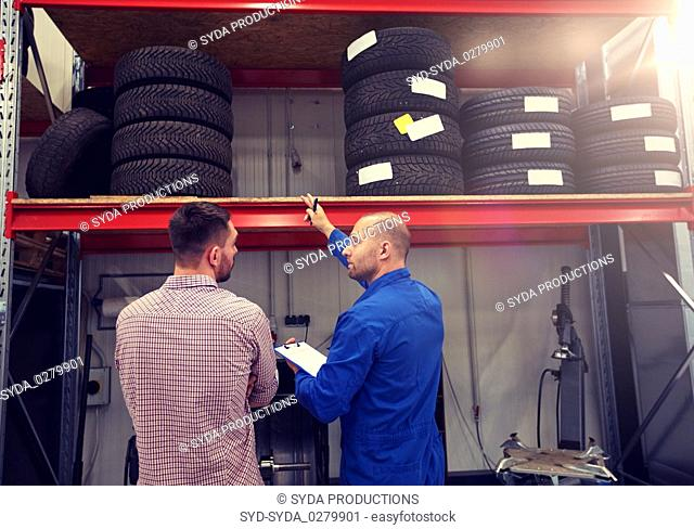 auto mechanic and man with tires at car shop