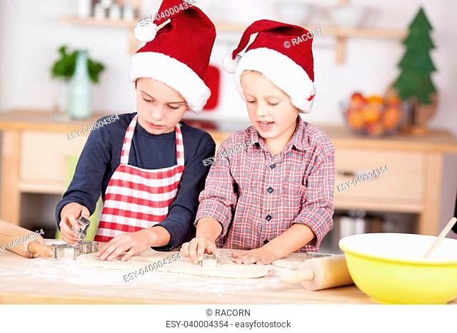Two cute Caucasian boys wearing Santa's hats and preparing Christmas cookies with shapes