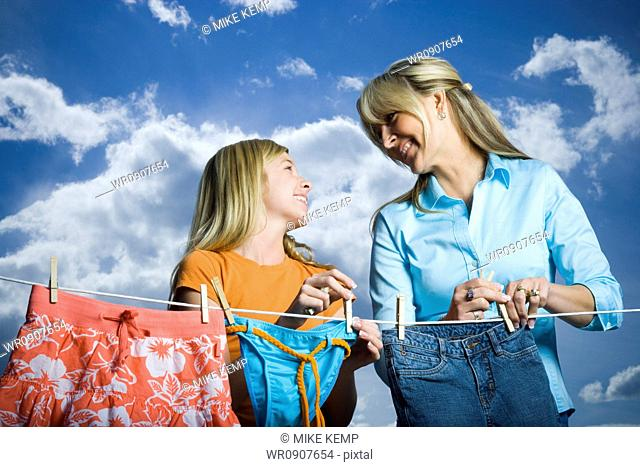 Close-up of a mother and her daughter looking at each other and smiling while doing laundry