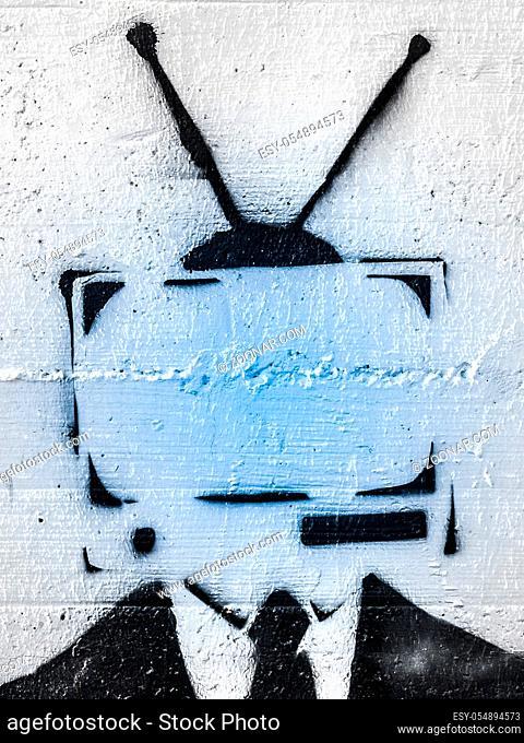 Addicted man holding vintage tv instead of head. Television manipulation and brainwashing concept. Mass media propaganda control