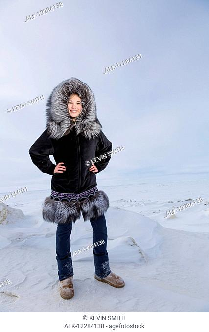 Female native youth wearing a traditional fur parka while standing on ice along the Arctic Ocean, Barrow, North Slope, Arctic Alaska, USA, Winter