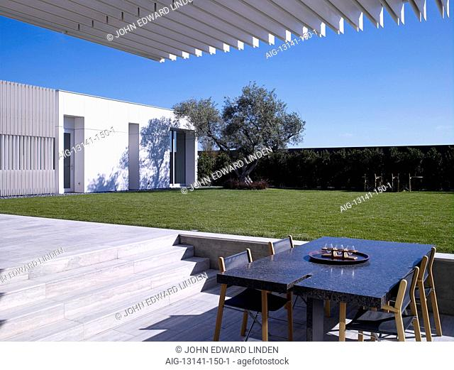 Modern detached house, West Hollywood, California. Shaded eating area with table and chairs