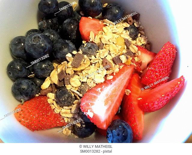 blueberries, strawberries and cereals in white bowl