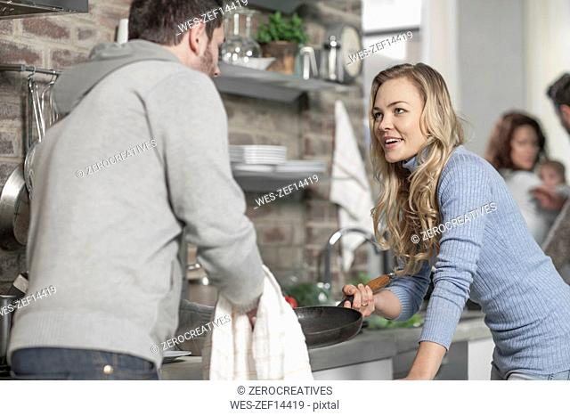 Couple discussing in kitchen while preparing a meal