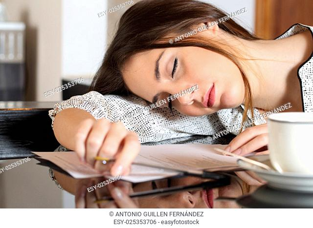 Tired overworked woman resting while she was working writing notes
