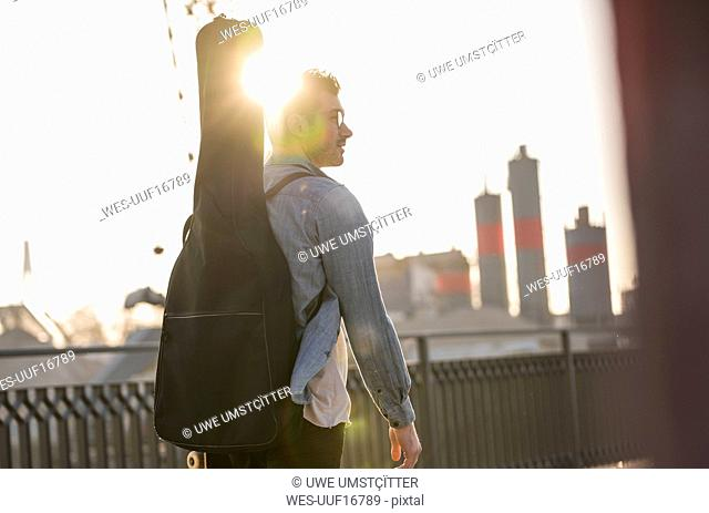 Young man with guitar case in the city at sunset