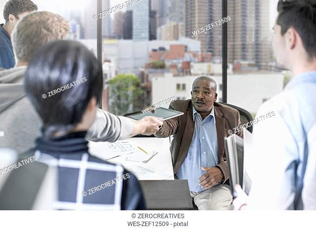 Businessman handing over digital tablet in office