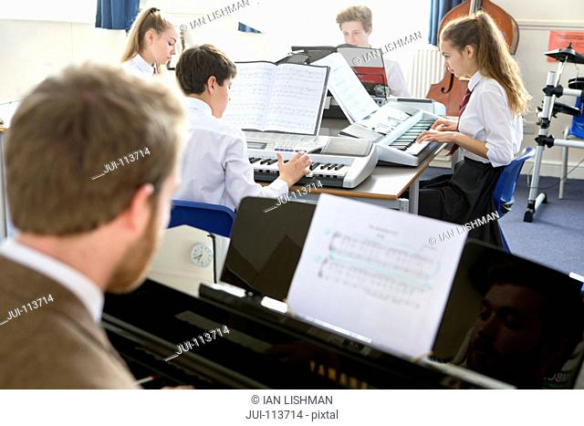 Music teacher teaching high school students playing piano in music class