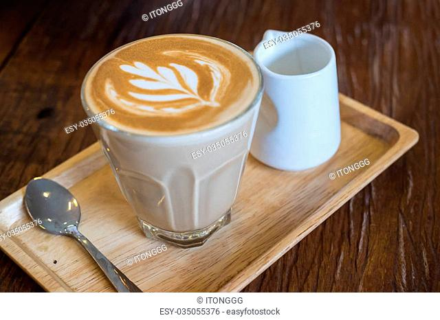 A glass of hot Piccolo latte coffee in wood tray on wooden table in cafe