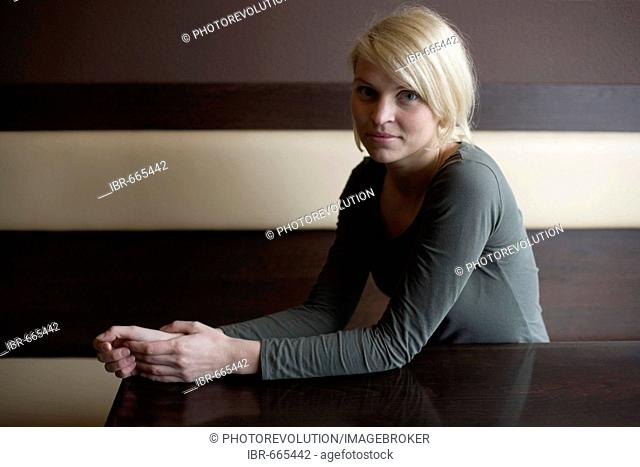 Blonde woman sitting at a table in a bar looking at camera
