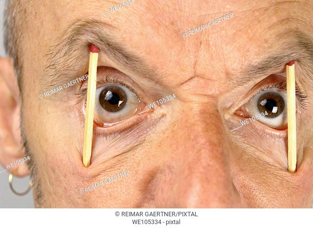 Close up of man keeping eyes wide open with match sticks