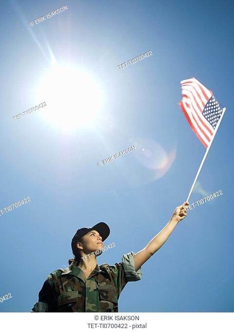 Female army soldier holding American flag