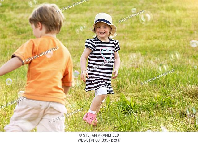 Two children trying to catch soap bubbles on a meadow