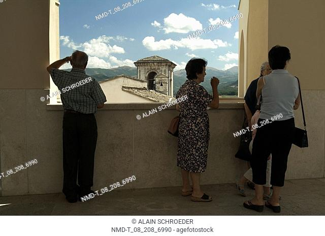 Four people standing near a window, Cascia, Umbria, Italy