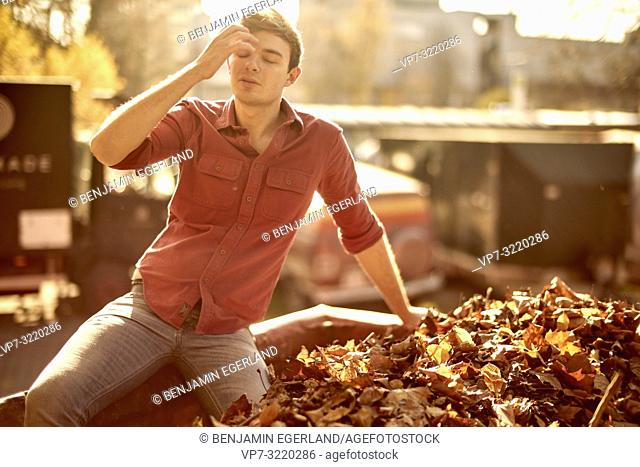 Young emotional man with closed eyes sitting in container full of autumn leaves, warm sunlight, in Munich, Germany