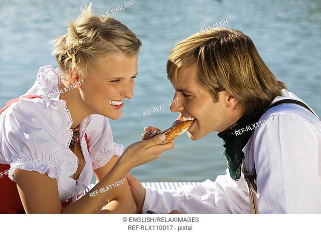Young couple in traditional Bavarian outfit, eating Pretzel, Munich