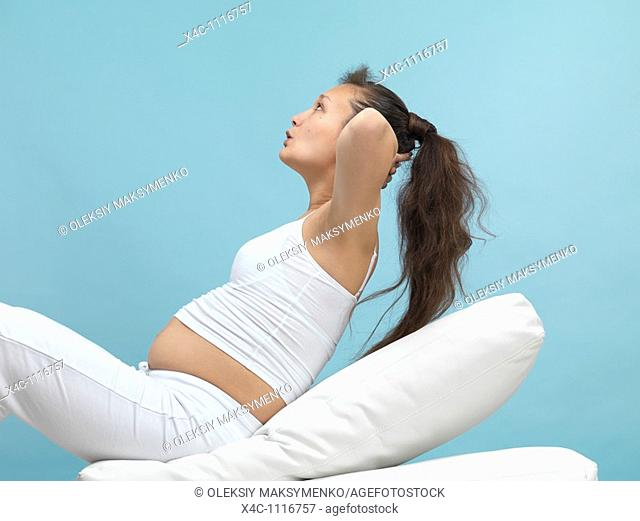 Pregnant young woman exercising doing crunches