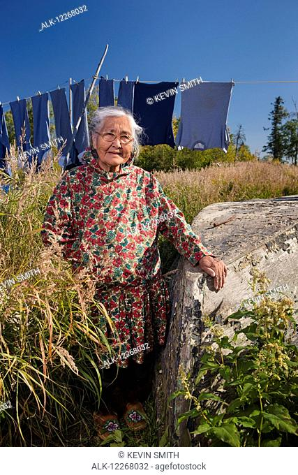 Female Alaskan native elder wearing a kuspuk posed next to an old boat with a clothesline in the background, Shungnak, Alaska, summer