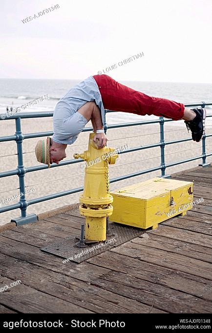 Man balancing on fire hydrant by railing at Santa Monica pier