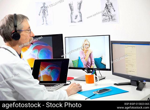 A GP during a video consultation looking at the x-ray of a woman's shoulder for shoulder pain