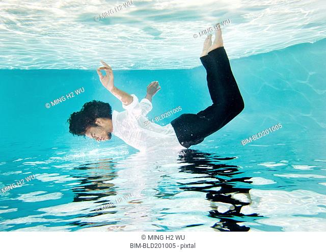 Mixed race man in clothes underwater in swimming pool