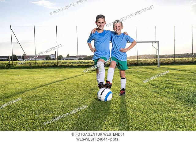 Smiling young football players embracing on football ground