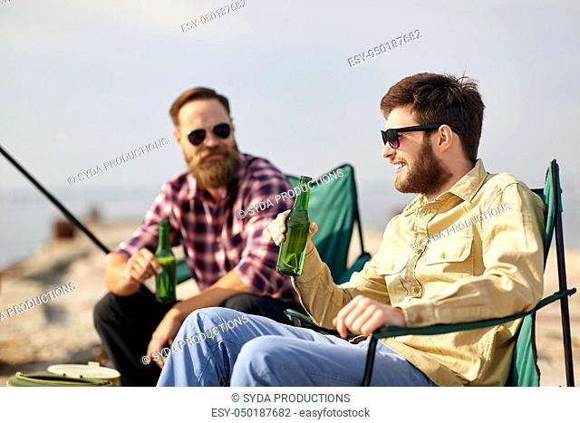 happy friends fishing and drinking beer on pier