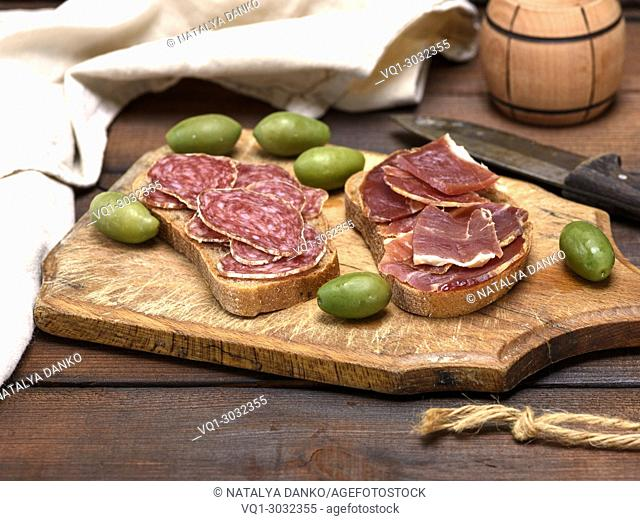 sandwiches with salami sausage and hamon on a brown wooden board, close up