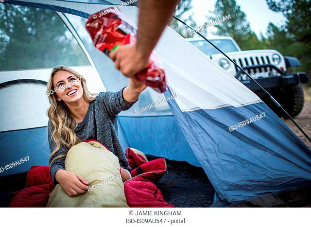 Young couple sharing snacks whilst camping, Lake Tahoe, Nevada, USA