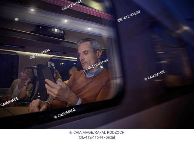 Businessman using smart phone at window on passenger train at night
