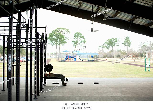 Silhouetted female soldier weightlifting barbell at air force military base