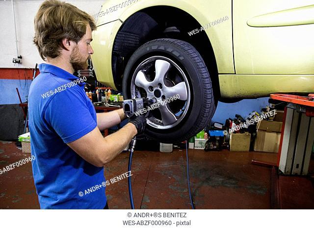 Mechanic fixing a car wheel in a workshop