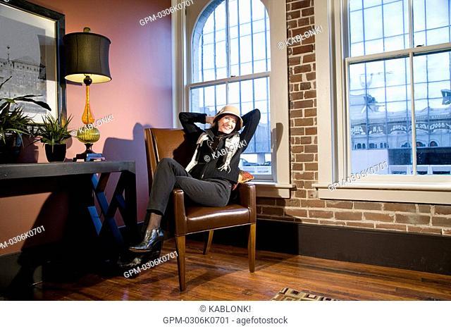 Portrait of mature woman sitting in modern downtown loft